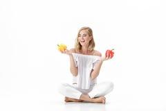 Schöne blonde Frau in der weißen Bluse, die gelben und roten grünen Pfeffer hält Gesunde Diät und Diät Lizenzfreie Stockbilder