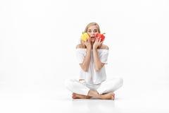 Schöne blonde Frau in der weißen Bluse, die gelben und roten grünen Pfeffer hält Gesunde Diät und Diät Stockfotos