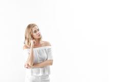 Schöne blonde Frau in der weißen Bluse und in den Hosen auf weißem Hintergrund Kopieren Sie spase Lizenzfreies Stockbild