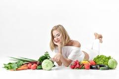 Schöne blonde Frau in der weißen Kleidung und in den vielen Frischgemüse auf weißem Hintergrund Lizenzfreies Stockbild