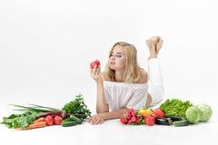 Schöne blonde Frau in der weißen Kleidung und in den vielen Frischgemüse auf weißem Hintergrund Mädchen, das Tomate hält Stockbilder