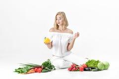 Schöne blonde Frau in der weißen Kleidung und in den vielen Frischgemüse auf weißem Hintergrund Mädchen hält grünen Pfeffer Lizenzfreie Stockfotografie