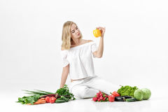 Schöne blonde Frau in der weißen Kleidung und in den vielen Frischgemüse auf weißem Hintergrund Mädchen hält grünen Pfeffer Stockbilder