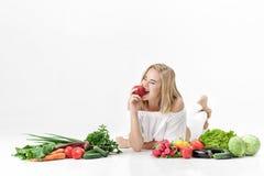 Schöne blonde Frau in der weißen Kleidung und in den vielen Frischgemüse auf weißem Hintergrund Mädchen isst Nektarine Lizenzfreie Stockbilder