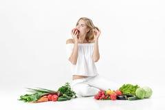Schöne blonde Frau in der weißen Kleidung und in den vielen Frischgemüse auf weißem Hintergrund Mädchen isst Nektarine Stockbilder