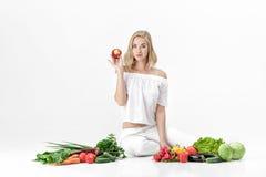 Schöne blonde Frau in der weißen Kleidung und in den vielen Frischgemüse auf weißem Hintergrund Mädchen isst Nektarine Stockfotografie