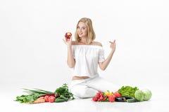 Schöne blonde Frau in der weißen Kleidung und in den vielen Frischgemüse auf weißem Hintergrund Mädchen isst Nektarine Stockbild