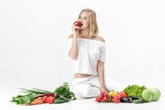 Schöne blonde Frau in der weißen Kleidung und in den vielen Frischgemüse auf weißem Hintergrund Mädchen isst Nektarine Lizenzfreie Stockfotografie