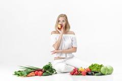 Schöne blonde Frau in der weißen Kleidung und in den vielen Frischgemüse auf weißem Hintergrund Mädchen isst Nektarine Stockfoto