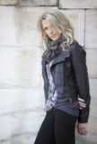 Schöne blonde Frau des blauen Auges, Stand gegen eine Wand Lizenzfreies Stockfoto