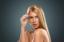 Schöne blonde Frau des Porträts mit dem langen Haar und den blauen Augen Stockfoto