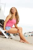 Schöne blonde Frau, die über den Strand lacht Lizenzfreies Stockbild