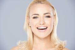 Schöne blonde Frau, die über die Kamera lacht Stockbild