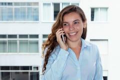 Schöne blonde Frau, die über Telefon lacht Stockbilder