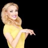 Schöne blonde Frau, die abwärts zeigt Stockbild