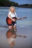 Schöne blonde Frau, die Akustikgitarre im Wasser spielt Stockfotos