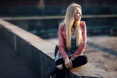 Schöne blonde Frau, die allein in der Straße auf Sonnenuntergang sitzt Stockfotografie