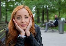 Schöne blonde Frau, die auf Bank sitzt Stockfotografie