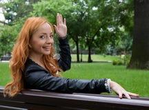 Schöne blonde Frau, die auf Bank sitzt Stockbild