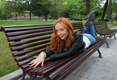 Schöne blonde Frau, die auf Bank sitzt Lizenzfreie Stockfotografie