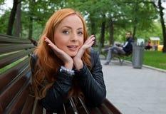 Schöne blonde Frau, die auf Bank sitzt Lizenzfreies Stockfoto