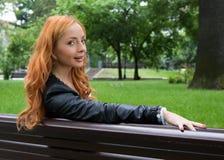 Schöne blonde Frau, die auf Bank sitzt Stockbilder