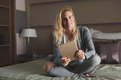 Schöne blonde Frau, die auf Bett sich entspannt Lizenzfreie Stockfotos