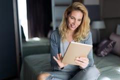 Schöne blonde Frau, die auf Bett sich entspannt Lizenzfreie Stockfotografie