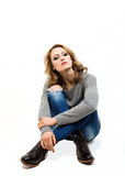Schöne blonde Frau, die auf Boden sitzt Stockfoto