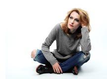 Schöne blonde Frau, die auf Boden sitzt Lizenzfreie Stockbilder