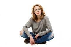 Schöne blonde Frau, die auf Boden sitzt Lizenzfreie Stockfotografie