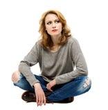 Schöne blonde Frau, die auf Boden sitzt Stockfotos