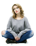 Schöne blonde Frau, die auf Boden sitzt Stockfotografie