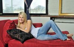 Schöne blonde Frau, die auf Couch sich entspannt Stockfotos