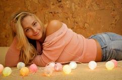 Schöne blonde Frau, die auf dem Bodenporträt, süßes Haus sitzt Lizenzfreie Stockbilder