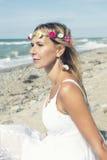Schöne blonde Frau, die auf dem Strand sitzt Lizenzfreie Stockfotos