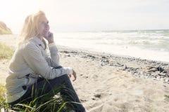 Schöne blonde Frau, die auf dem Strand sitzt Lizenzfreies Stockbild