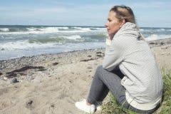 Schöne blonde Frau, die auf dem Strand sitzt Lizenzfreie Stockfotografie