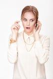 Schöne blonde Frau, die auf dem Telefon und den Spielen mit dem Haar spricht Lizenzfreie Stockbilder