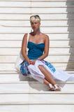 Schöne blonde Frau, die auf den Treppen sitzt Stockfotos