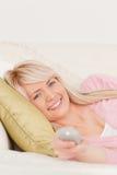 Schöne blonde Frau, die auf einem Sofa aufwirft Stockbild