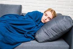 Schöne blonde Frau, die auf einer Couch eingewickelt in einer blauen Decke liegt Lizenzfreies Stockfoto