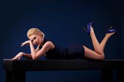 Schöne blonde Frau, die auf einer Tabelle liegt Stockfotografie