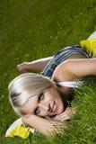 Schöne blonde Frau, die auf grünem Gras sich entspannt Lizenzfreie Stockfotos