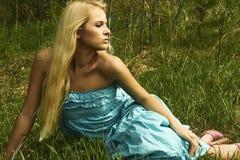 Schöne blonde Frau, die auf grünem Gras sitzt Lizenzfreie Stockfotografie