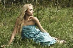 Schöne blonde Frau, die auf grünem Gras sitzt Stockbilder
