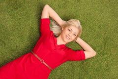 Schöne blonde Frau, die auf Gras in einer Wiese liegt Lizenzfreie Stockfotos