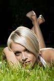 Schöne blonde Frau, die auf Gras liegt Stockfoto