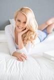 Schöne blonde Frau, die auf ihrem Bett sich entspannt Stockfoto