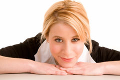 Schöne blonde Frau, die auf ihrem Schreibtisch aufwirft Lizenzfreie Stockfotos